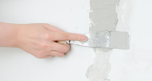 Female hand repairs wall Royalty Free Stock Image