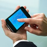 Female hand reviewing information on smart phone. Stock Photography