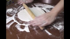 Female hand rolled fresh dough on the table with the help of a rolling pin. Close up stock footage
