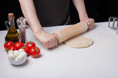 Female hand rolled pizza dough with a rolling pin on a white table, sprinkled with flour.  Royalty Free Stock Images