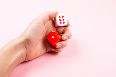 Female hand rolling dices with hearts royalty free stock photos