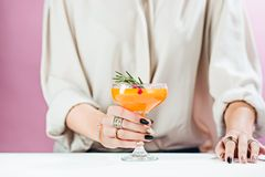 The rose exotic cocktails and fruits and female hand. The female hand and rose exotic cocktail and fruits on table Royalty Free Stock Images