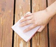 Female hand sanding cedar wood deck Royalty Free Stock Photography