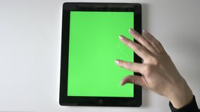 Female hand scrolling on tablet. Green screen, chromakey concept, Top shot 60 fps. 4k stock footage