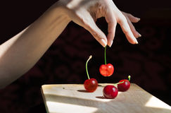Female hand selecting a cherry. A female hand is selecting a cherry from a wooden table Royalty Free Stock Photos