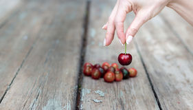 Female hand selecting a cherry stock photo