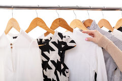 Female hand selects new fashion clothes on wood hangers on rack, Royalty Free Stock Photos