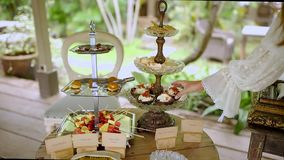 Female hand selects sweetness among the appetizers on the buffet. Wooden terrace with vegetation in the background. Gourmet and fo. Od in the hotels concept stock footage