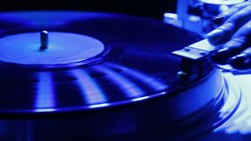 Female hand sets a turntable needle on a vinyl record in color light. Close-up stock video footage