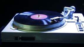 Female hand sets a turntable needle on a vinyl record in color light. Hd stock footage