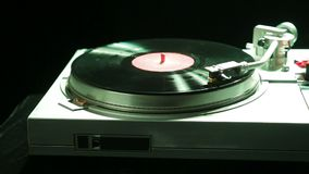 Female hand sets a turntable needle on a vinyl record in color light. Hd stock video footage