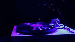 Female hand sets a turntable needle on a vinyl record in color light. Hd stock video