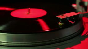 Female hand sets a turntable needle on a vinyl record in disco light. Hd stock video footage