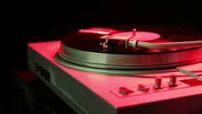 Female hand sets a turntable needle on a vinyl record in disco light. Hd stock video