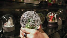 Beautiful winter snow globe with Christmas tree inside. Slow motion.