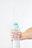 Female hand shaking small bottle of fresh water with splash Stock Photography