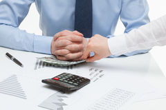 Female hand shoving money under business partner's hand Royalty Free Stock Image