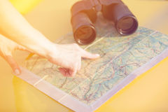 Female hand show a point at map near a binoculars Royalty Free Stock Photo