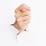 Female hand showing a fig sign. Through a torn paper Royalty Free Stock Images