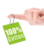 Female hand showing hundred percent cotton tag. Isolated on white background Royalty Free Stock Photos