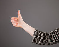 Female hand showing positive gesture. On grey background Stock Photography