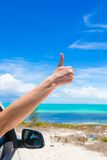 Female hand showing thumbs up on the beach Stock Photos