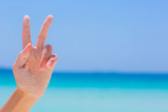 Female hand showing victory sympbol on sea background. Female hand showing victory sympbol on blue sky and sea background Stock Photography