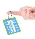 Female hand showing warranty tag royalty free stock photo
