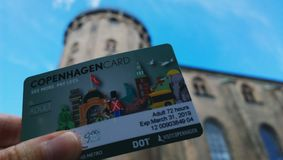Female hand shows a Copenhagen card on the background of Round Tower. The card allows you to visit many museums. And use public transport in the city Stock Photos