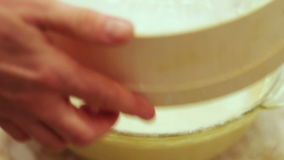 Female hand sifted flour through a sieve. In a transparent container with dough stock footage