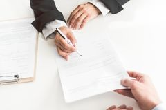Female hand signing agreement at desk royalty free stock photos