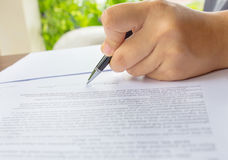 Female hand signing contract. Stock Image