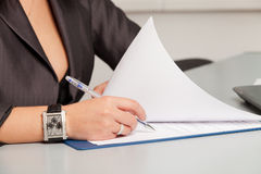 Female hand signing contract. Stock Photos