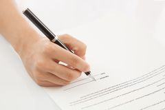 Female hand signing contract. royalty free stock images