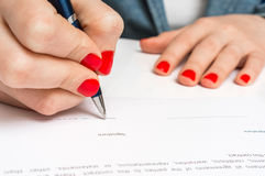 Female hand signing contract to conclude a deal. Female hand signing business contract to conclude a deal royalty free stock photo