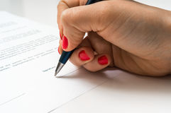 Female hand signing contract to conclude a deal. Female hand signing business contract to conclude a deal stock image