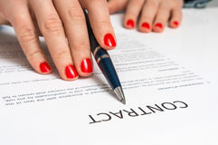 Female hand signing contract to conclude a deal. Female hand signing business contract to conclude a deal stock images