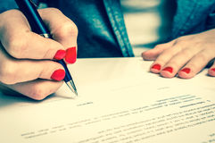 Female hand signing contract to conclude a deal. Female hand signing business contract to conclude a deal - retro style stock photos