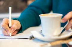 Female hand signing in notebook and drinking coffee, on bright background. In a blue clothes stock image