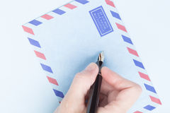 Female hand signs airmail envelope Stock Image