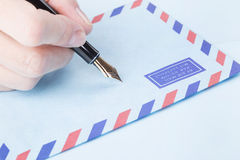 Female hand signs airmail envelope Stock Photography