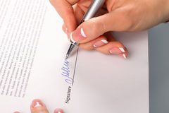 Female hand signs business letter. Stock Photos