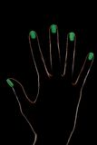 Female hand silhouette with phosphorescent nail polish. Female hand silhouette on black background with contour lighting and green luminescent nail design Royalty Free Stock Photos