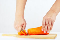 Female hand slices carrots Royalty Free Stock Image