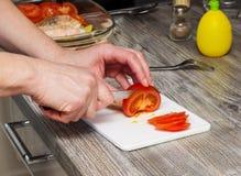 Female hand slicing a fresh garden tomato Stock Photo