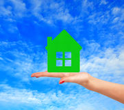 Female hand with small model of house over blue sky Stock Images