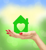 Female hand with small model of house over blurred nature backgr Royalty Free Stock Photography