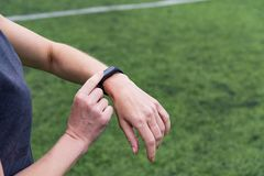 Female hand with smart watch on green outdoor sports stadium background royalty free stock images