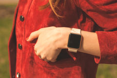 Female hand with smart watches in pocket of red jacket Stock Photography