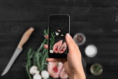Female hand with a smartphone makes a photo raw chicken breast on black background, with fresh mushrooms, garlic and. Herbs. Cooking ingredients, healthy eating Stock Photos